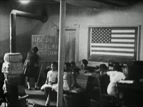 stockvideo's en b-roll-footage met 1964 black and white black schoolchildren in classroom / girl writing on chalkboard / prince edward county, va - racisme