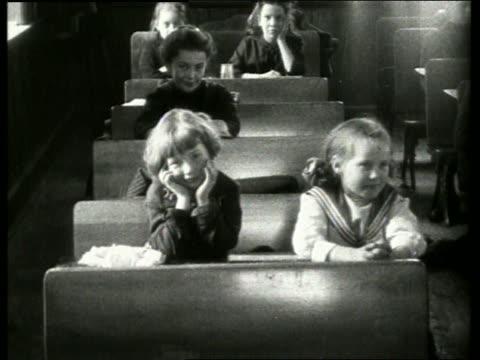 Black and white children sitting at desks in classroom / NO AUDIO