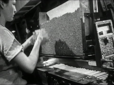 1950 black and white cigarette factory worker picking up cigarettes from assembly line and putting on large stack - cigarette stock videos & royalty-free footage