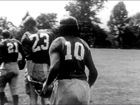 1953 black and white close up boy strapping on football helmet / pan to boy jumping on back of teammate and rolling around on football field / other boys watching them wrestle / audio - play fight stock videos and b-roll footage