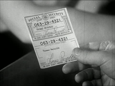 1940 black and white close up hand holding social security card - 社会保障点の映像素材/bロール