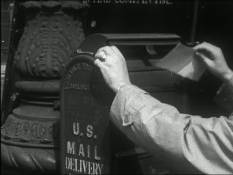 vídeos de stock, filmes e b-roll de 1949 black and white close up hands putting letter in mailbox / new york city - sending