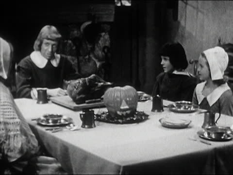 1960 black and white close up jack-o-lantern / medium shot zoom out recreation of pilgrm family thanksgiving dinner / saying grace - pellegrino video stock e b–roll