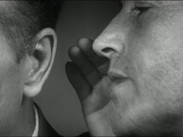 vidéos et rushes de 1952 black and white close up man whispering into another man's ear - 1952