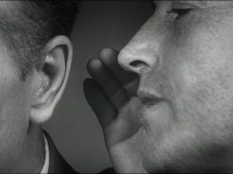 1952 black and white close up man whispering into another man's ear - saggezza video stock e b–roll