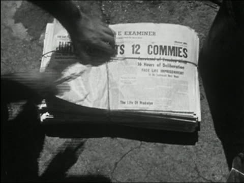 "stockvideo's en b-roll-footage met ""1955 black and white close up man's hand cutting string from newspaper bundle with headline ""jury convicts 12 commies"""" - communisme"