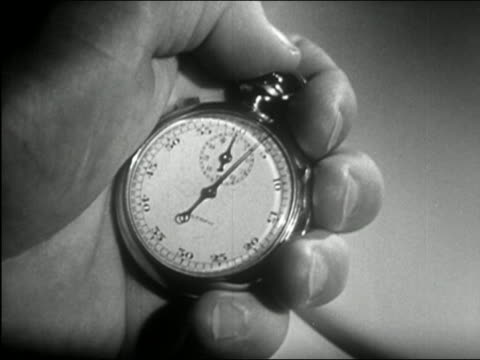 stockvideo's en b-roll-footage met 1950 black and white close up man's hands holding ticking stopwatch - klok