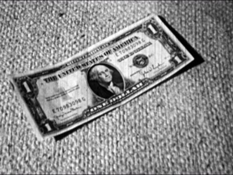 1953 Black and white close up of a US dollar bill / person placing a Susan B. Anthony silver dollar next to it / AUDIO