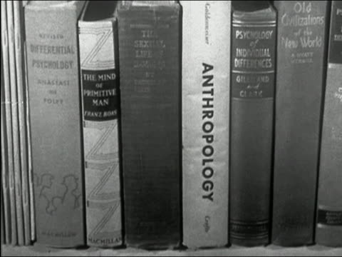 1957 black and white close up psychology and anthropology books on shelf / 'Sexual Life of Savages' popping out