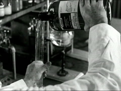 1939 Black and white close up scientist pouring poison into large test tube/ AUDIO
