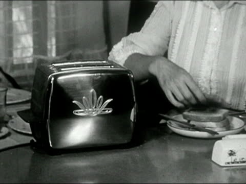 1958 black and white close up toaster/ zoom out medium shot woman at breatkfast table putting bread in toaster and drinking from coffee cup/ audio - toaster appliance stock videos & royalty-free footage