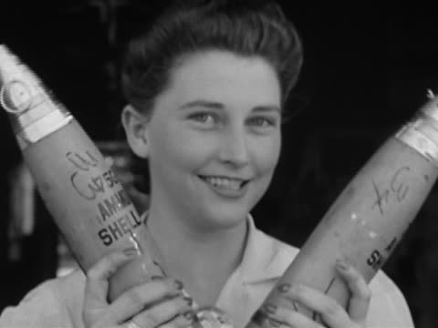 vidéos et rushes de black and white close up woman smiling as she holds two ammunition shells / aberdeen proving ground, maryland - 1942