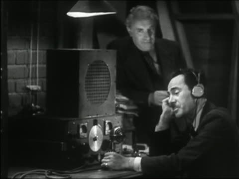 1941 black and white close up zoom out to medium shot man at desk talking into radio transmitter while other man watches in background