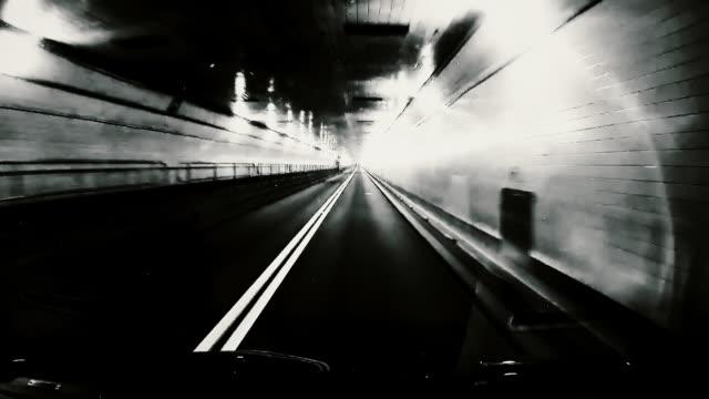 vídeos de stock e filmes b-roll de black and white dashboard camera point of view of driving through tunnel - preto e branco