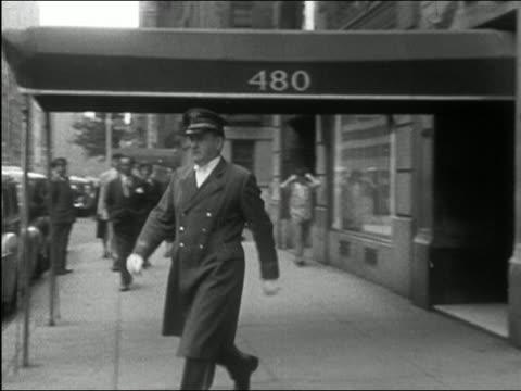 1949 black and white doorman opening car door for wealthy apartment resident / new york city - 1949 bildbanksvideor och videomaterial från bakom kulisserna