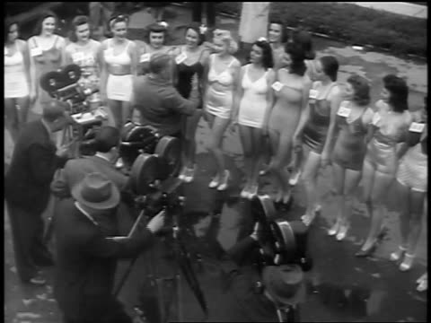 black and white early 1940s high angle swimsuit contest models standing in front of motion picture cameras / newsreel - in front of stock videos & royalty-free footage