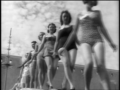 black and white early 1940s low angle swimsuit contest models walking past camera outdoors / newsreel /audio - beauty contest stock videos and b-roll footage