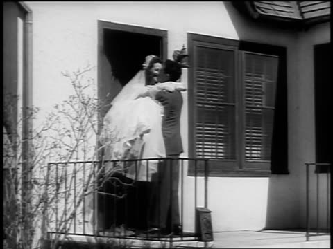 black and white early 1940s man carrying bride over threshold of house / newsreel /audio - bride 個影片檔及 b 捲影像