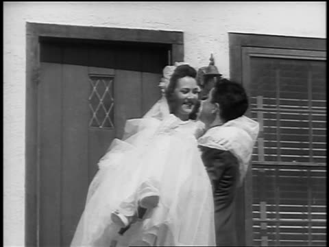 Black and white early 1940s man carrying bride towards threshold of house / newsreel /AUDIO