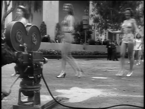 black and white early 1940s swimsuit contest models walk past running motion picture camera outdoors / newsreel - beauty pageant stock videos and b-roll footage