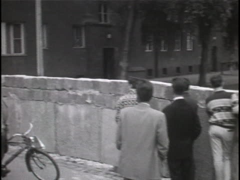 ws black and white footage a group of spectators on foot and bicycles gather on the west berlin side of the newly constructed berlin wall which is... - (war or terrorism or election or government or illness or news event or speech or politics or politician or conflict or military or extreme weather or business or economy) and not usa stock-videos und b-roll-filmmaterial