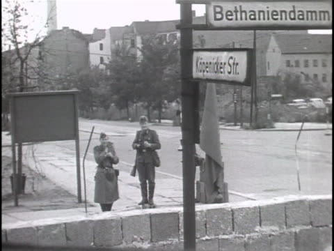 ext ws black and white footage of two east german border guards talking together on a street corner are seen from the western side of the newly... - (war or terrorism or election or government or illness or news event or speech or politics or politician or conflict or military or extreme weather or business or economy) and not usa stock-videos und b-roll-filmmaterial