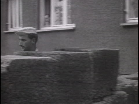ms black and white footage of workmen laying bricks to build up a section of the wall on harzer strasse as east german border guards are seen nearby... - (war or terrorism or election or government or illness or news event or speech or politics or politician or conflict or military or extreme weather or business or economy) and not usa stock-videos und b-roll-filmmaterial