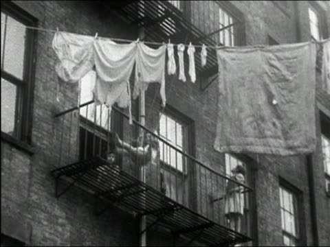 1949 black and white girl pushing another on fire escape swing below clothesline / new york city - fire escape stock videos & royalty-free footage