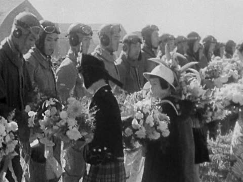 black and white girls present japanese pilots with bouquets of flowers at ceremony - pacific war video stock e b–roll