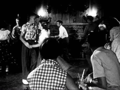vídeos de stock e filmes b-roll de 1953 black and white group of teenage boys and girls square dancing  / audio - dança quadrada