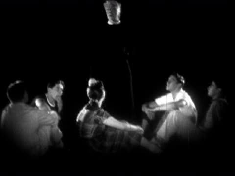 1954 Black and white group of teenagers sitting in a circle looking up at a woman wearing a double-faced mask / AUDIO