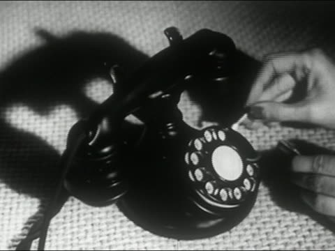 1944 black and white hand holding lit match up to phone receiver to demonstrate durability of plastic technology - durability stock videos and b-roll footage