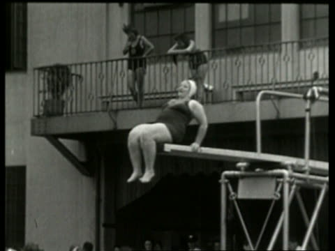 black and white heavy woman sits then dives from diving board / no audio - one piece swimsuit stock videos & royalty-free footage
