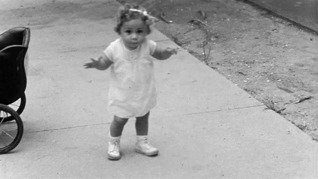 vídeos de stock e filmes b-roll de 1934 black and white high angle close up little girl toddling on sidewalk and smiling at cam / huntington, long island, ny - infância