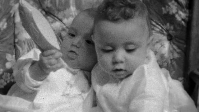 1933 black and white high angle close up two babies sitting close together and looking up / passing toy fish
