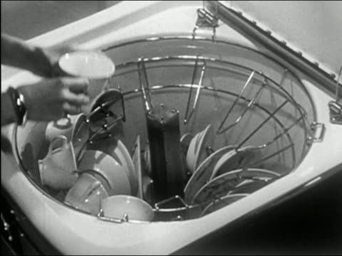 1950 black and white high angle close up woman's hands loading top-loading dishwasher / pouring soap powder in cup - lavastoviglie video stock e b–roll