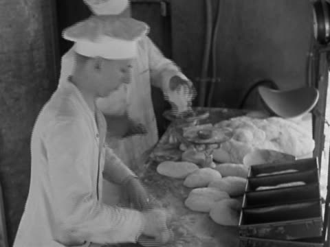1942 black and white high angle medium shot bakers weighing and kneading dough / placing rolled dough in baking pans / Camp Lee VA