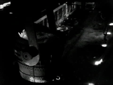 1936 black and white high angle medium shot large ladle of molten steel travelling over steelworks floor - metal blend stock videos and b-roll footage