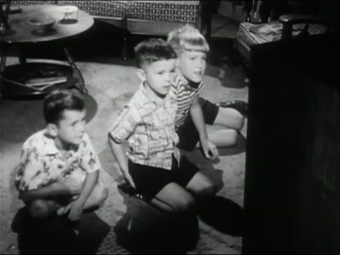1956 black and white high angle medium shot three young boys watching tv and shooting at the screen / audio - 1950点の映像素材/bロール