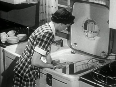 1950 black and white high angle medium shot woman in kitchen loading top-loading dishwasher - lavastoviglie video stock e b–roll