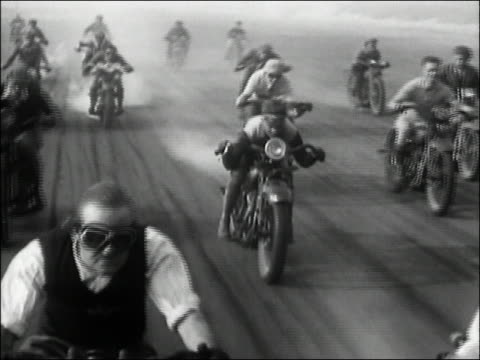 vídeos de stock, filmes e b-roll de 1929 black and white high angle wide shot tracking shot motorcyclists racing on ocean beach track / california - 1920 1929