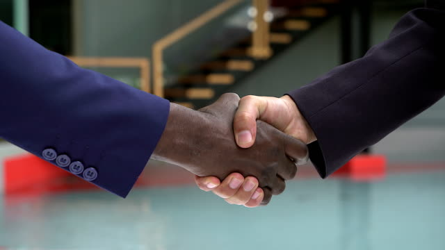 black and white human hands with business clothing in a modern handshake to show each other friendship and respect. - handshake stock videos and b-roll footage