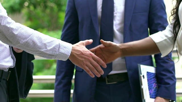 Black and white human hands with business clothing in a modern handshake to show each other friendship and respect.