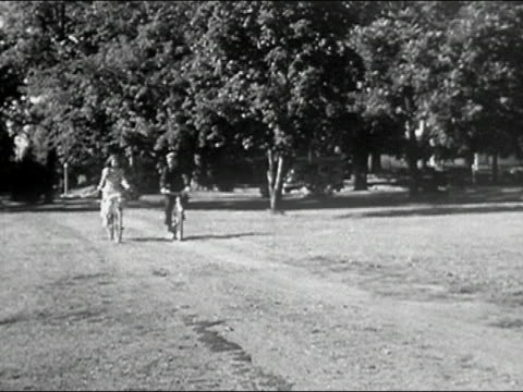 1950 black and white long shot pan young man and woman riding bikes in park / man performing stunt / columbia, missouri - handlebar stock videos & royalty-free footage