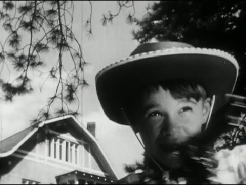 1956 black and white low angle close up young boy dressed as cowboy shooting toy guns / audio - toy gun stock videos & royalty-free footage