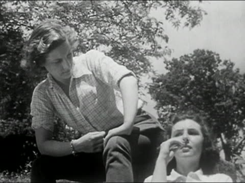 1950 black and white low angle medium shot two young women chewing straw and chatting under tree / columbia, missouri - gossip stock videos & royalty-free footage