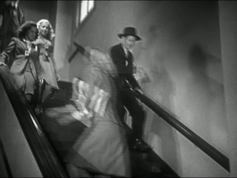 1944 black and white low angle wide shot businessman rushing down stairs / slipping and falling - careless stock videos & royalty-free footage