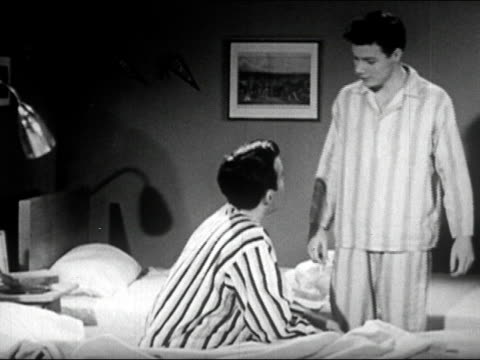 1950 black and white / male college roommates saying, 'Good night,' before going to bed in dorm room / turning off light and getting into beds / audio