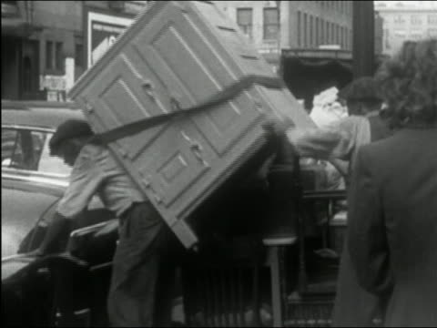 vidéos et rushes de 1949 black and white man carrying large chest onto curb and putting down with other furniture / new york city - carrying