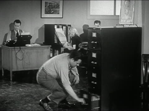 1944 black and white man getting file from file cabinet/ neglecting to close drawer/ woman tripping over drawer
